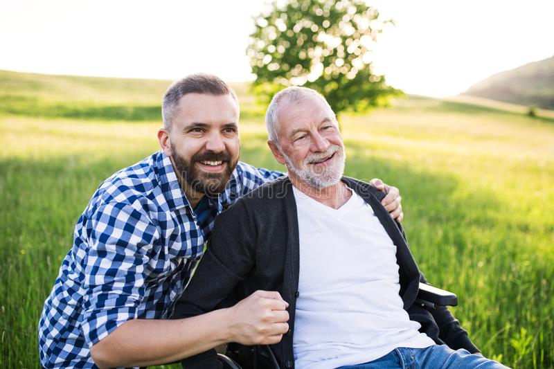 An adult hipster son with senior father in wheelchair on a walk in nature at sunset, laughing. royalty free stock photography