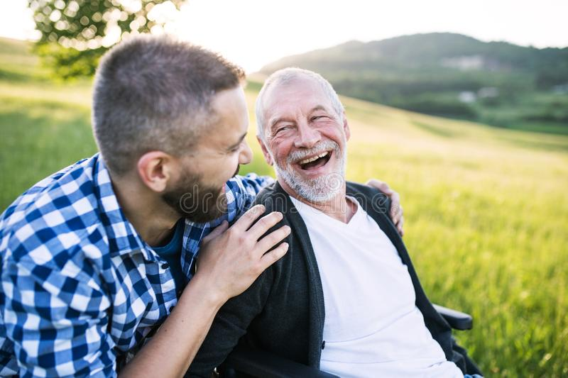 An adult hipster son with senior father in wheelchair on a walk in nature at sunset, laughing. royalty free stock image