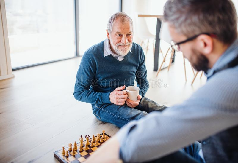 An adult hipster son and senior father sitting on floor indoors at home, playing chess. royalty free stock photography