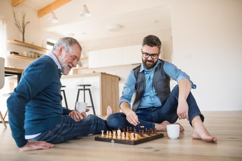 An adult hipster son and senior father sitting on floor indoors at home, playing chess. royalty free stock image