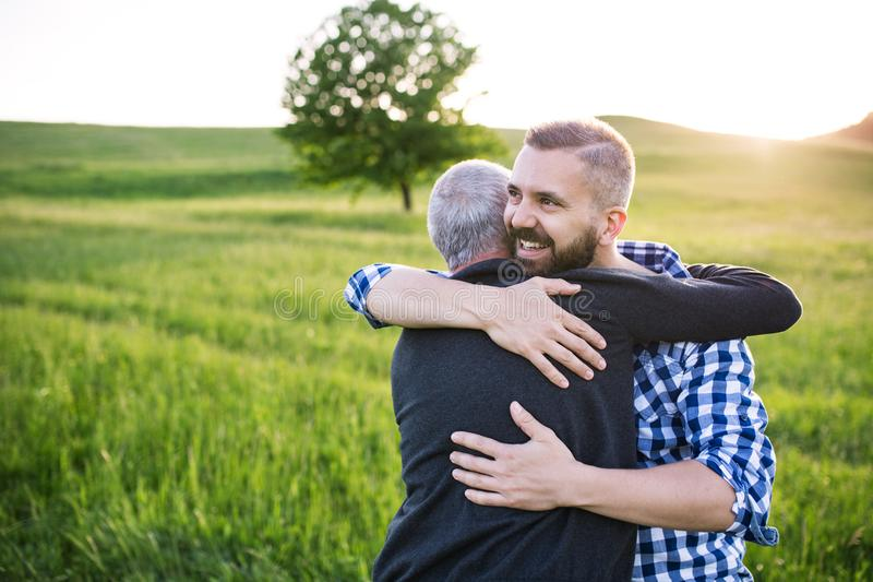 An adult hipster son with senior father on a walk in nature at sunset, hugging. royalty free stock photography