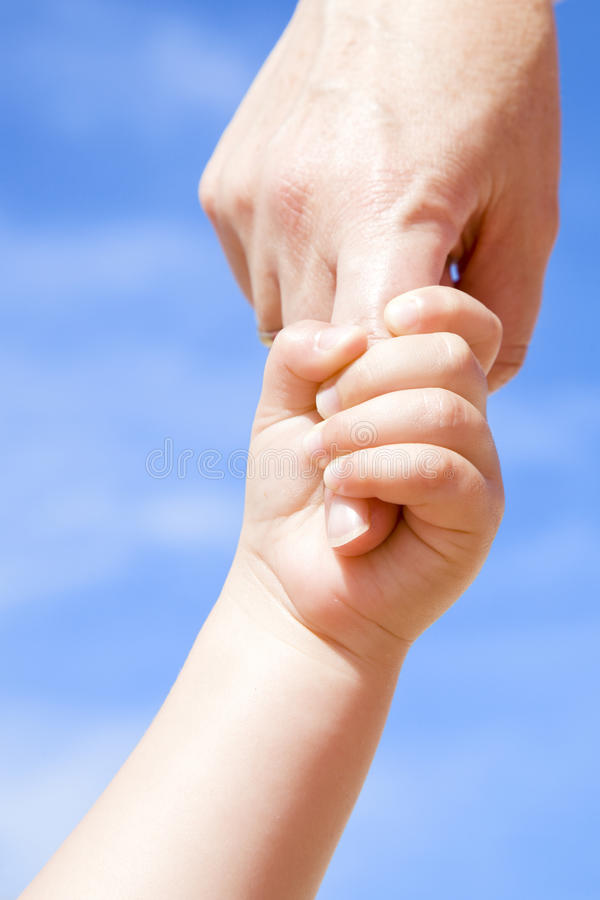 Adult giving hand to a child. Cute image of an adult giving hand to a child with a cloudy blue sky as background royalty free stock photos
