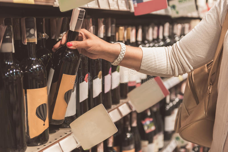 Adult lady buying alcohol in shop royalty free stock photos