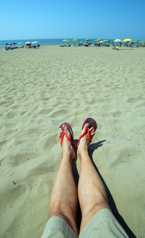 Adult with long legs and flip flops at the foot rests on the san. Young adult with long legs and flip flops at the foot rests on the sand during the summer royalty free stock photography