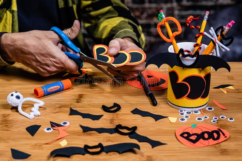 An Adult male cutting `Boo` from construction paper working on Halloween crafts at a table. royalty free stock photos
