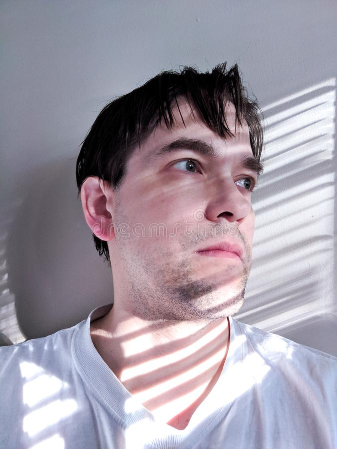 Adult Male in Deep Contemplation as Morning Light Falls Across His Face stock image