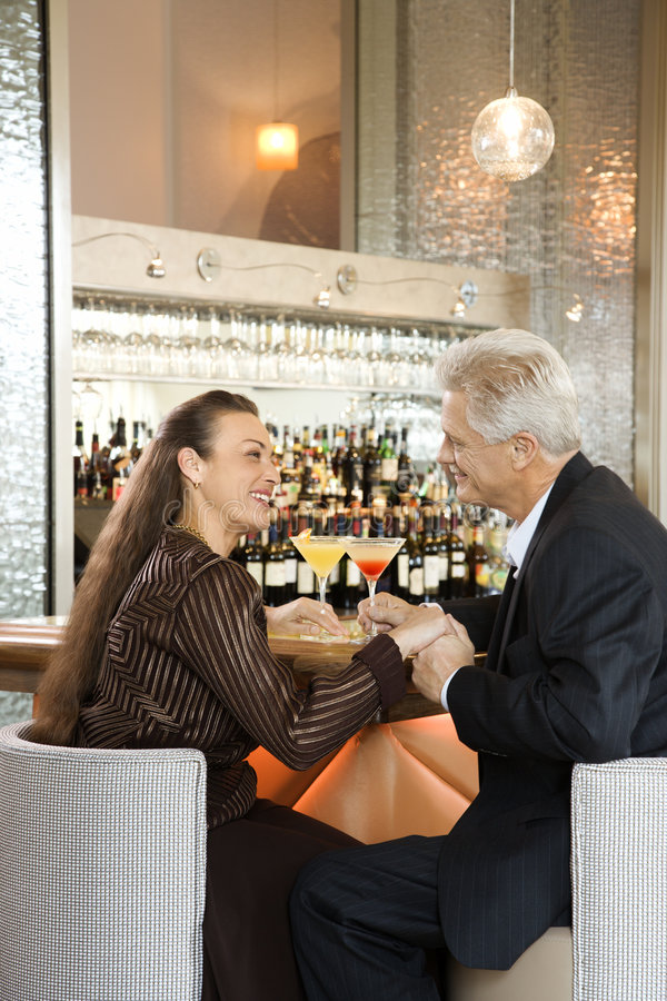 Adult male and female at bar holding hands. stock image