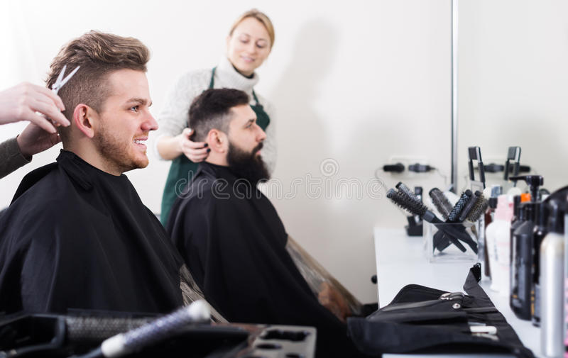 Adult male having their hair cut by hairdressers. At hair salon royalty free stock image