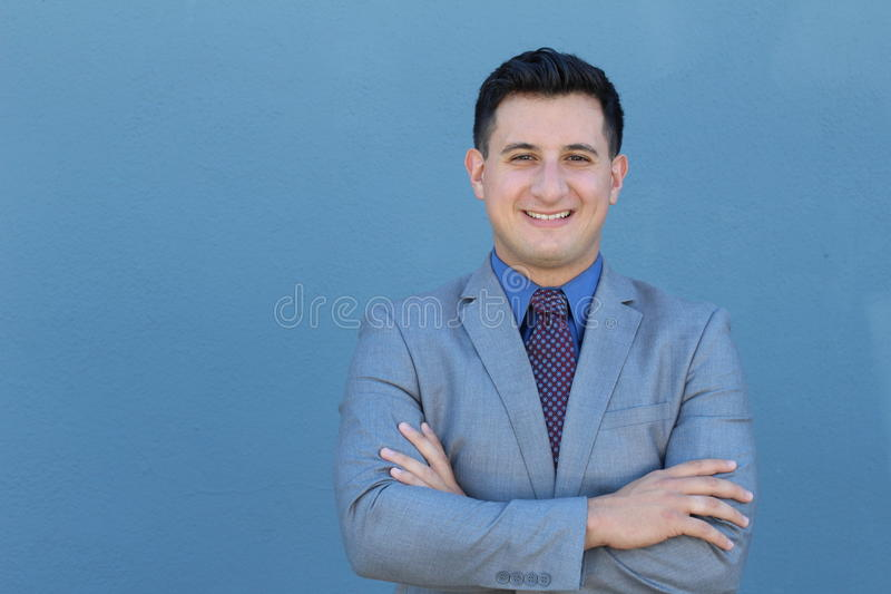 An adult male in his early thirties wearing suit, tie and shirt with crossed arms. He is smiling while crossing his arms royalty free stock photos