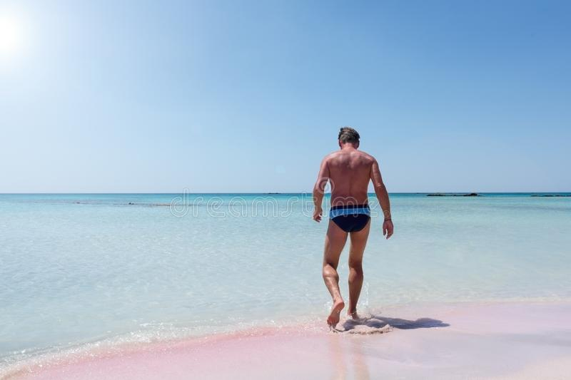 Adult male on the pink sand beach at Elafonisi on the island of. Crete in summer stock images