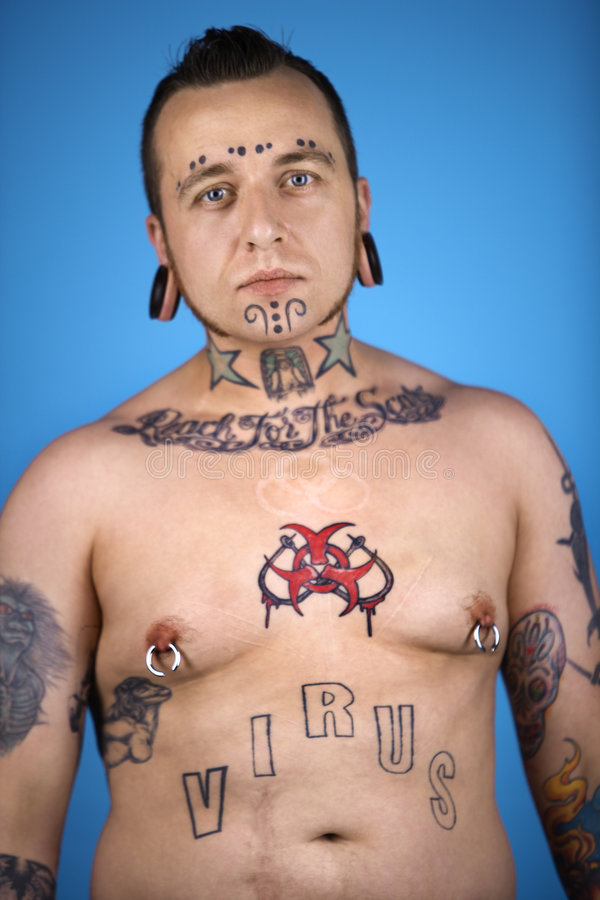 Adult male with tattoos and piercings. Barechested Caucasian mid-adult man with tattoos and piercings stock image