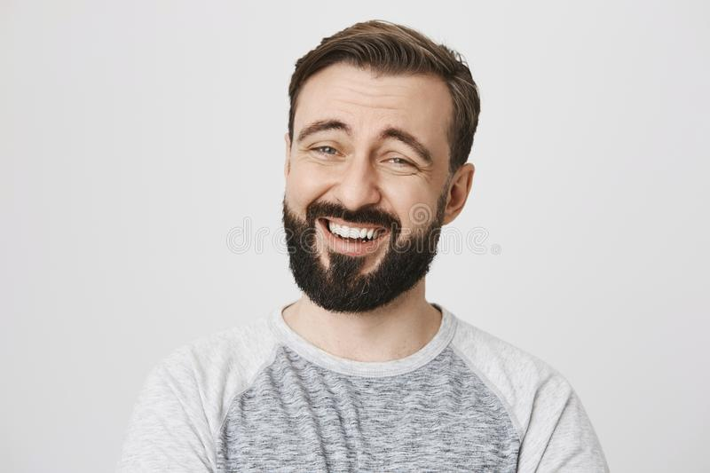 Adult man with beard and moustache laughing looking at the camera over white background. Handsome brunette is watching royalty free stock photo