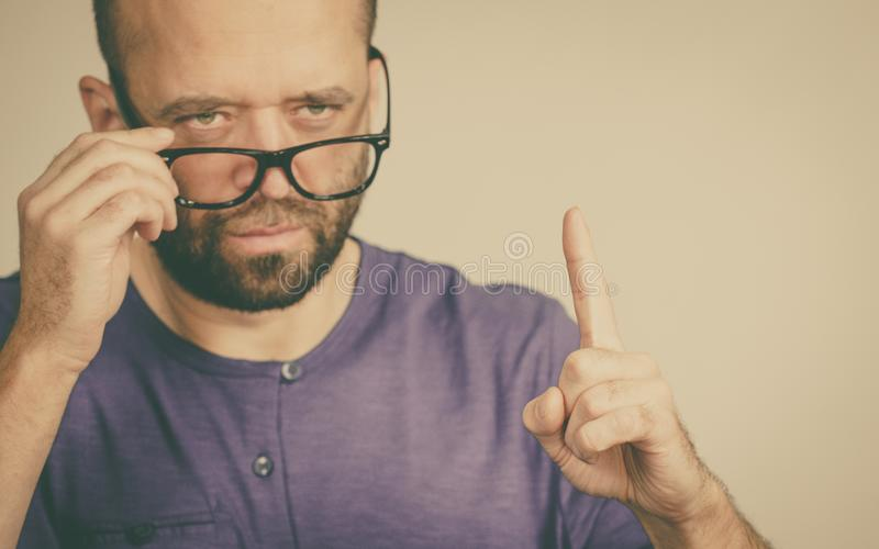 Adult man being angry pointing with finger. Adult rude man wearing eyeglasses being overbearing, commanding pointing with his finger royalty free stock images