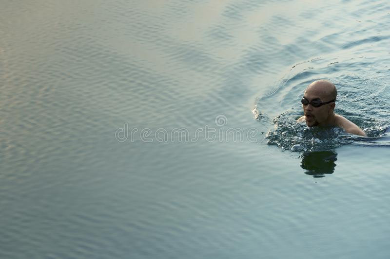 Adult man with black goggle swim in the summer blue green lake water for travel vacation background royalty free stock image