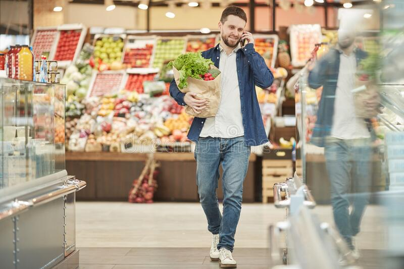 Adult Man Calling by Smartphone in Supermarket stock photos