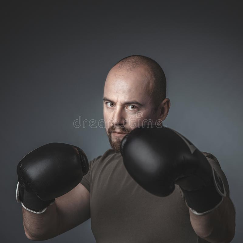 Adult man with casual clothes and boxing gloves, looks directly at the camera royalty free stock photos