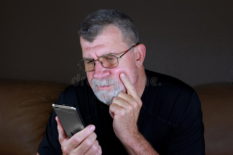 Adult Man Contemplates His Mobile Phone royalty free stock image