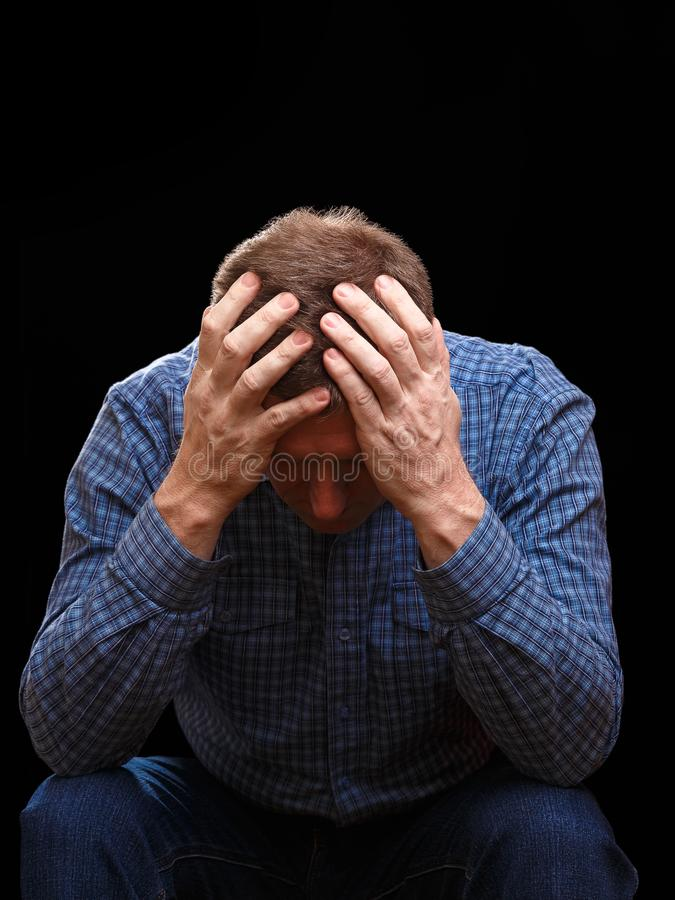 Adult man covers his head with his hands looking down royalty free stock photography