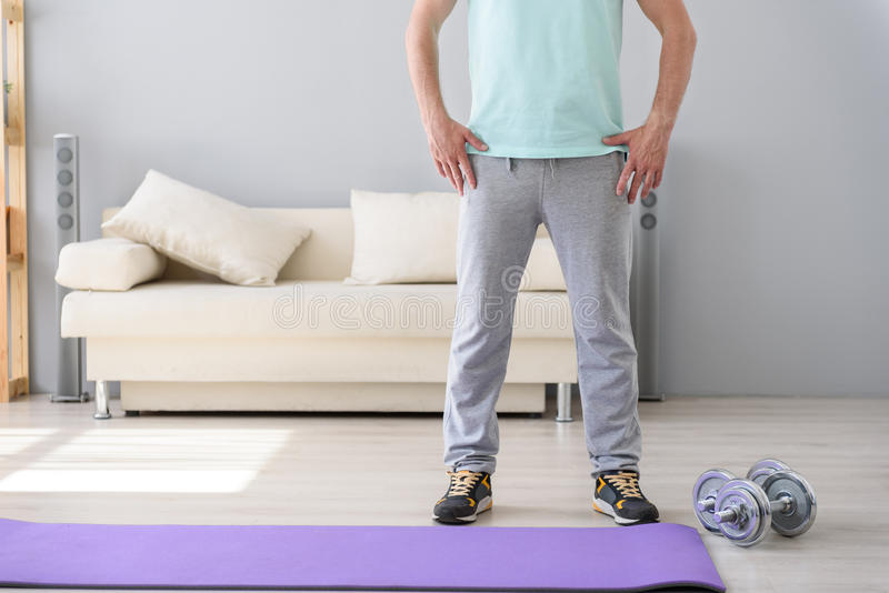 Adult man doing exercises at home stock photo
