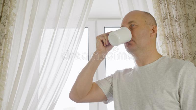 Adult man drinking morning coffee on cozy kitchen on window background. Portrait cheerful man enjoying hot tea from cup stock photo