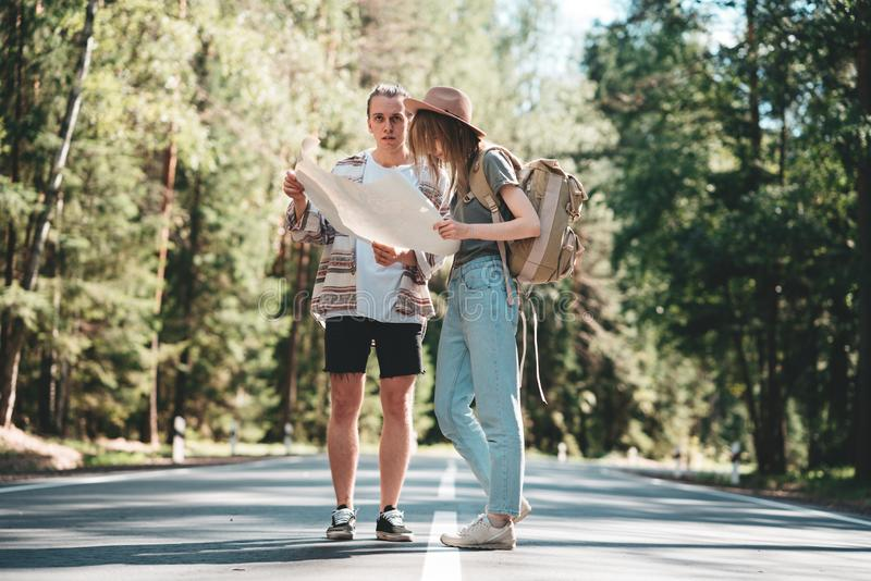 Adult man and girl traveling together on forest road. Young hipster couple travelers looking on the location map. Adult men and girl traveling together on forest royalty free stock image