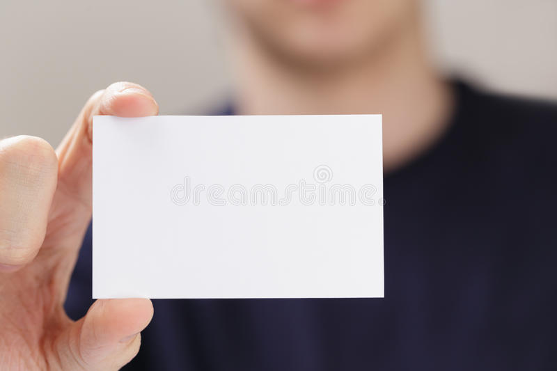 Adult man hand holding empty business card in front of camera stock image