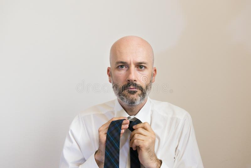 One mid age man with beard is knotting his necktie stock photography