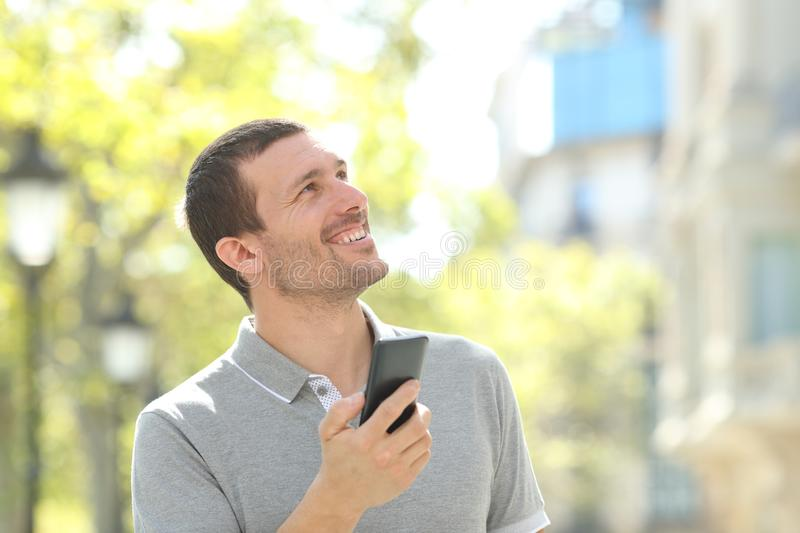 Adult man holding phone searching location in the street royalty free stock photo