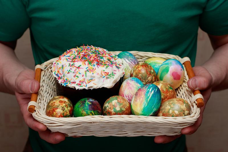 An adult man holds a basket with an easter cake and easter eggs in download an adult man holds a basket with an easter cake and easter eggs in his negle Images