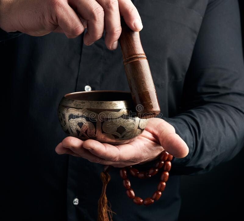 Free Adult Man In A Black Shirt Rotates A Wooden Stick Around A Copper Tibetan Bowl Of Water. Ritual Of Meditation Stock Images - 170823504