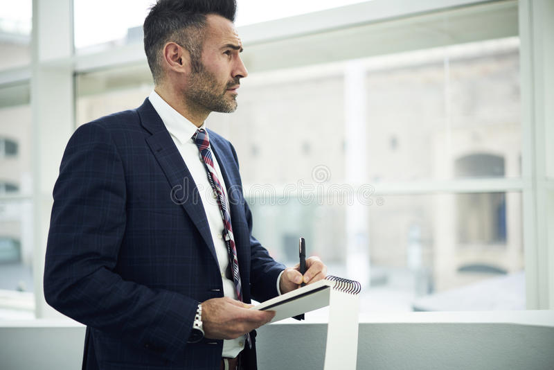Adult man in a jacket and glasses advertising campaign to attract customers writing down best ideas into notebook royalty free stock photography