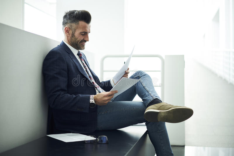 Adult man in a jacket and glasses affairs admiring work of skilled author sitting in office stock image