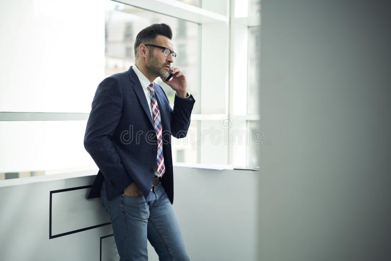 Adult man in a jacket and glasses coworking space controlling work of office being on business trip abroad stock photo