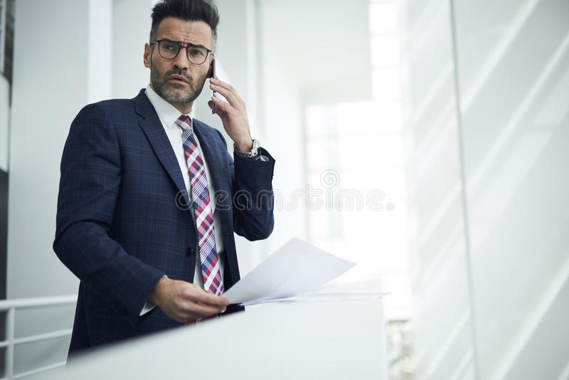Adult man in a jacket and glasses. Experienced male executive in elegant formal wear looking through documentation while having telephone conversation with stock photos