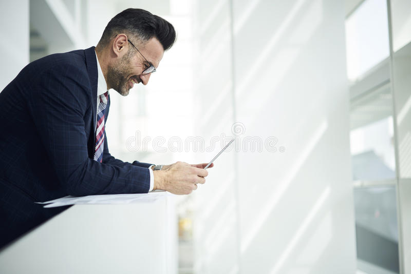 Adult man in a jacket and glasses startup project increasing rate of sales and income using gadget and wifi stock photos