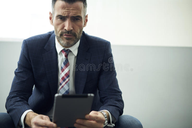 Adult man in a jacket and glasses trading company via portable pc connected to free wireless internet in coworking stock photos
