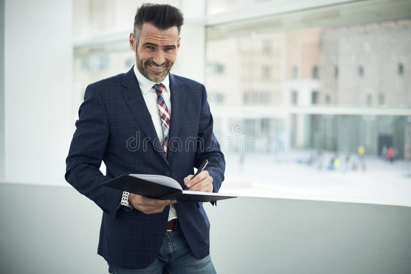 Adult man in a jacket and glasses uture publication in notebook while standing in modern coworking space royalty free stock images