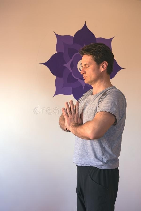 Adult man in yoga studio, practicing mindfulness. Adult man practicing mindfulness, in yoga studio stock photography