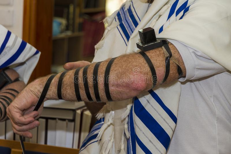 An adult man putting a Jewish Tefillin on his arm and wearing prayer shawl for praying royalty free stock photos