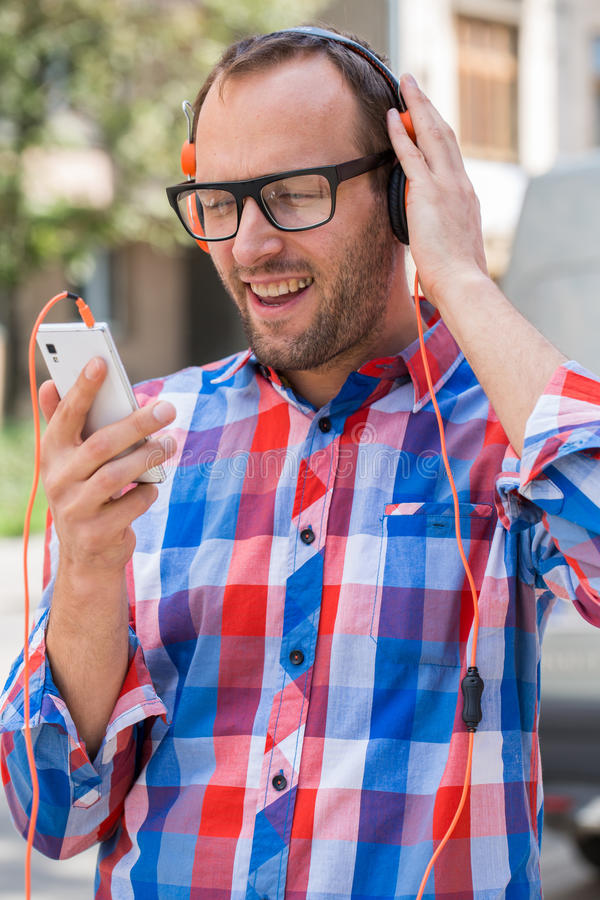 Adult man relaxing with headphones, listening to music. Orange f. Ashionable headphones. He is dressed in shirts Checked. Outdoor royalty free stock image
