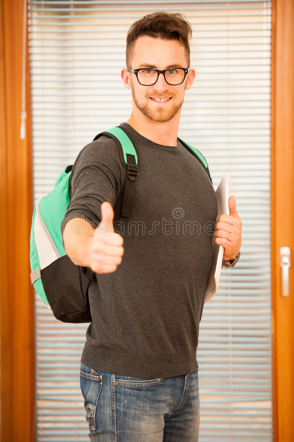 Adult man representing lifelong learning. Man with school bag sh. Owing thumb up as a gesture of happiness and joy to study stock images