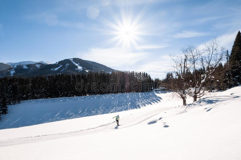 Adult man running cross-country skiing in snow-covered holiday resort Hohentauern. With the mountain Kleiner Schober in the background stock photos