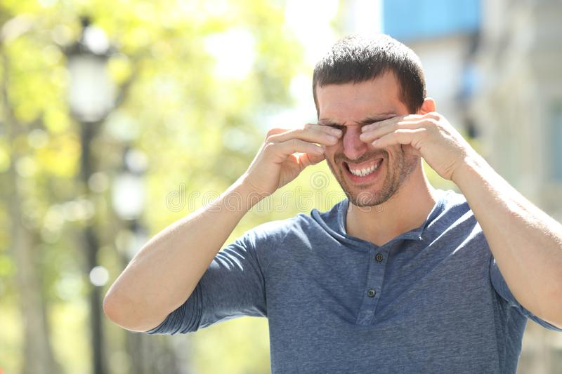 Adult man scratching itchy eyes in the street. Adult man scratching itchy eyes with both hands standing in the street royalty free stock photo