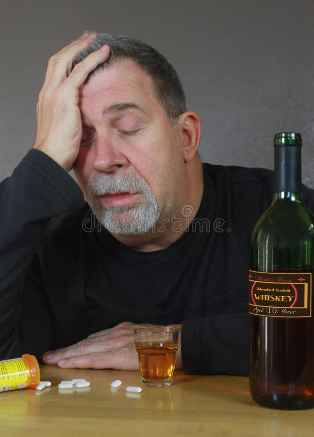 Adult Man Self Medicates with Booze and Pills stock images