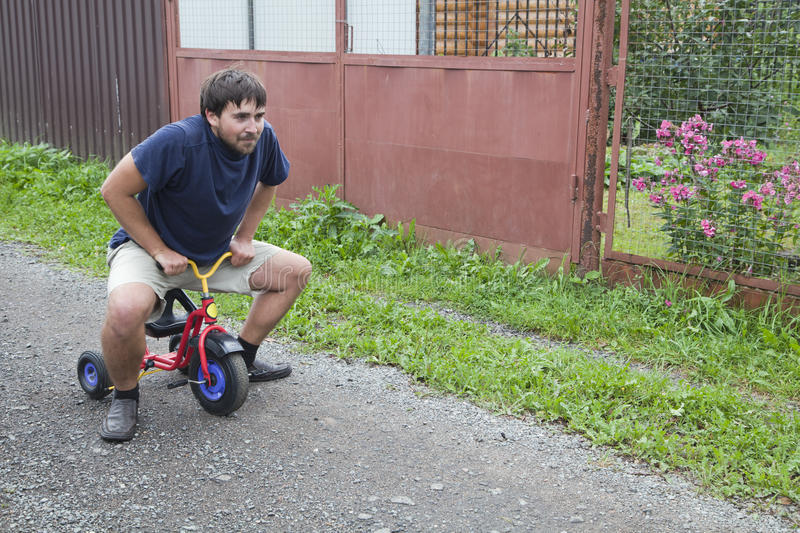 Adult man on a small tricycle. Adult man tying to ride on a small tricycle stock photos