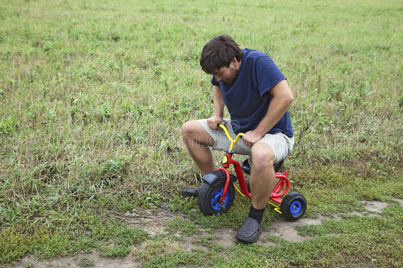 Adult man on a small tricycle. Adult man tying to ride on a small tricycle royalty free stock photography