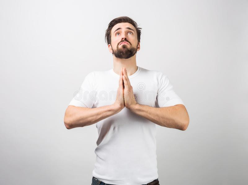Adult man is standing on the floor and praying. Suring the prayer he is looking up. This guy is probably a believer royalty free stock photo
