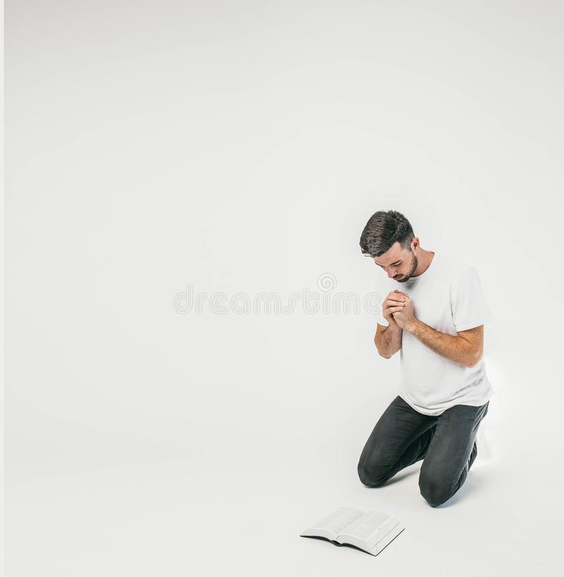 Adult man is standing on his knees and praying while his eyes are looking down to the floor. There is a Bible in the stock images