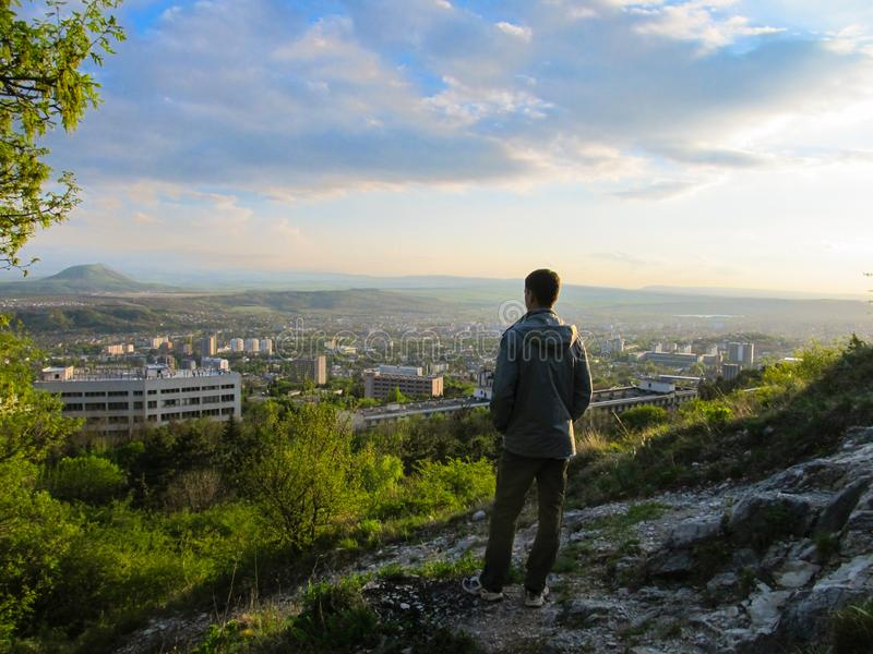 Adult man stands on top of a mountain and looks at the beautiful landscape at sunset stock photography
