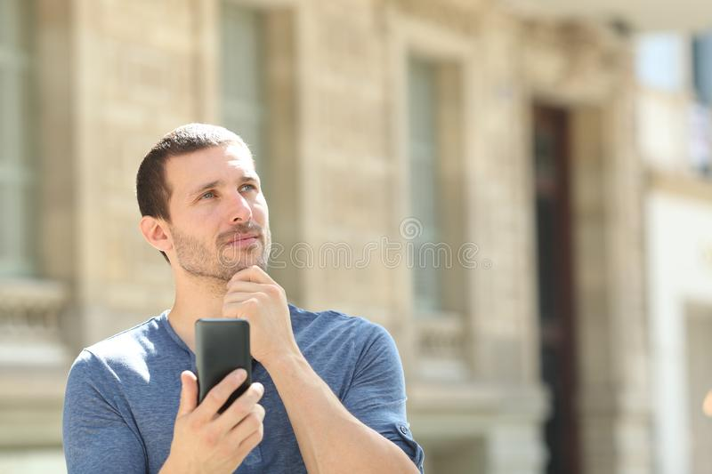 Adult man thinking holding smart phone in the street royalty free stock photography